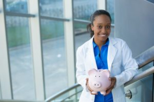 female dentist holding pink glass piggy bank