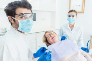 a female patient lying back in the chair while the dentist and dental hygienist, both wearing personal protective equipment, look on