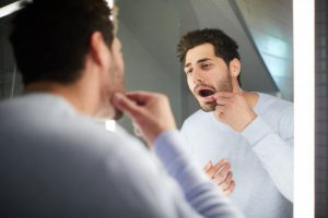 man looking at his mouth in a mirror to see if he needs to replace dental fillings