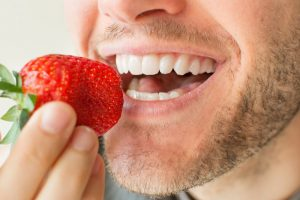 man preparing to eat strawberry