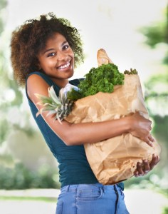 woman with a beautiful smile and a bag full of healthy groceries thanks to the dentist flint, MI trusts