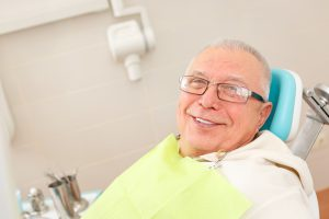 older man smiling in dental chair